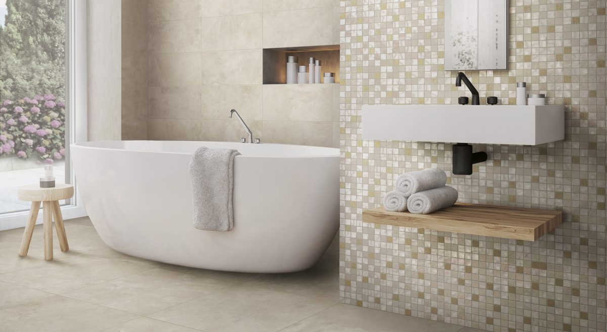 Cream bathroom with mosaic tiles and a white bath