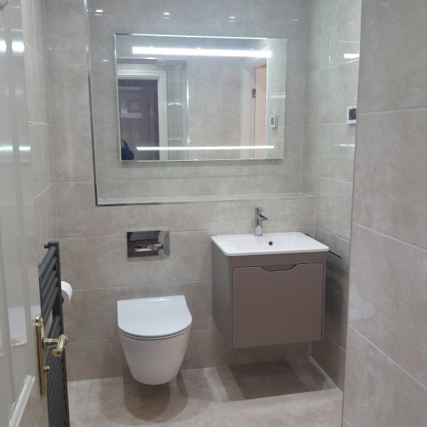 Back lighted mirror in ensuite bathroom with grey and white colour scheme