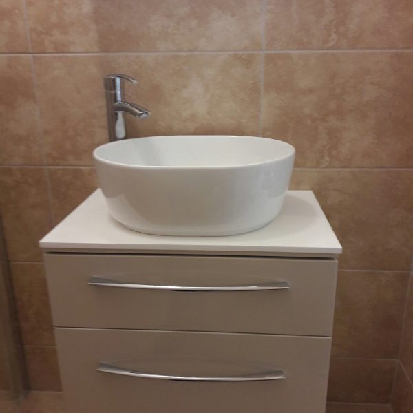 White basin in ensuite with brown tiles